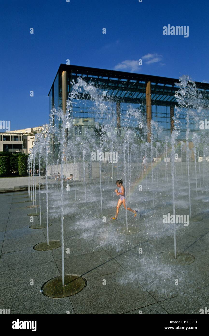 little girl playing with water jets at Parc Andre Citroen, 15th arrondissement, Paris, Ile de France region, France, - Stock Image