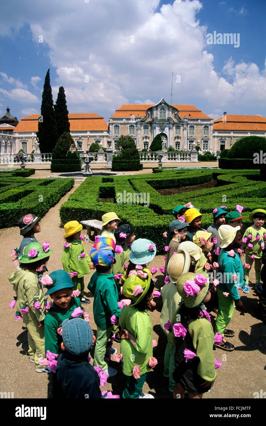children in the gardens in front of the facade of the ballroom wing, Queluz National Palace, Portugal, Southern - Stock Image
