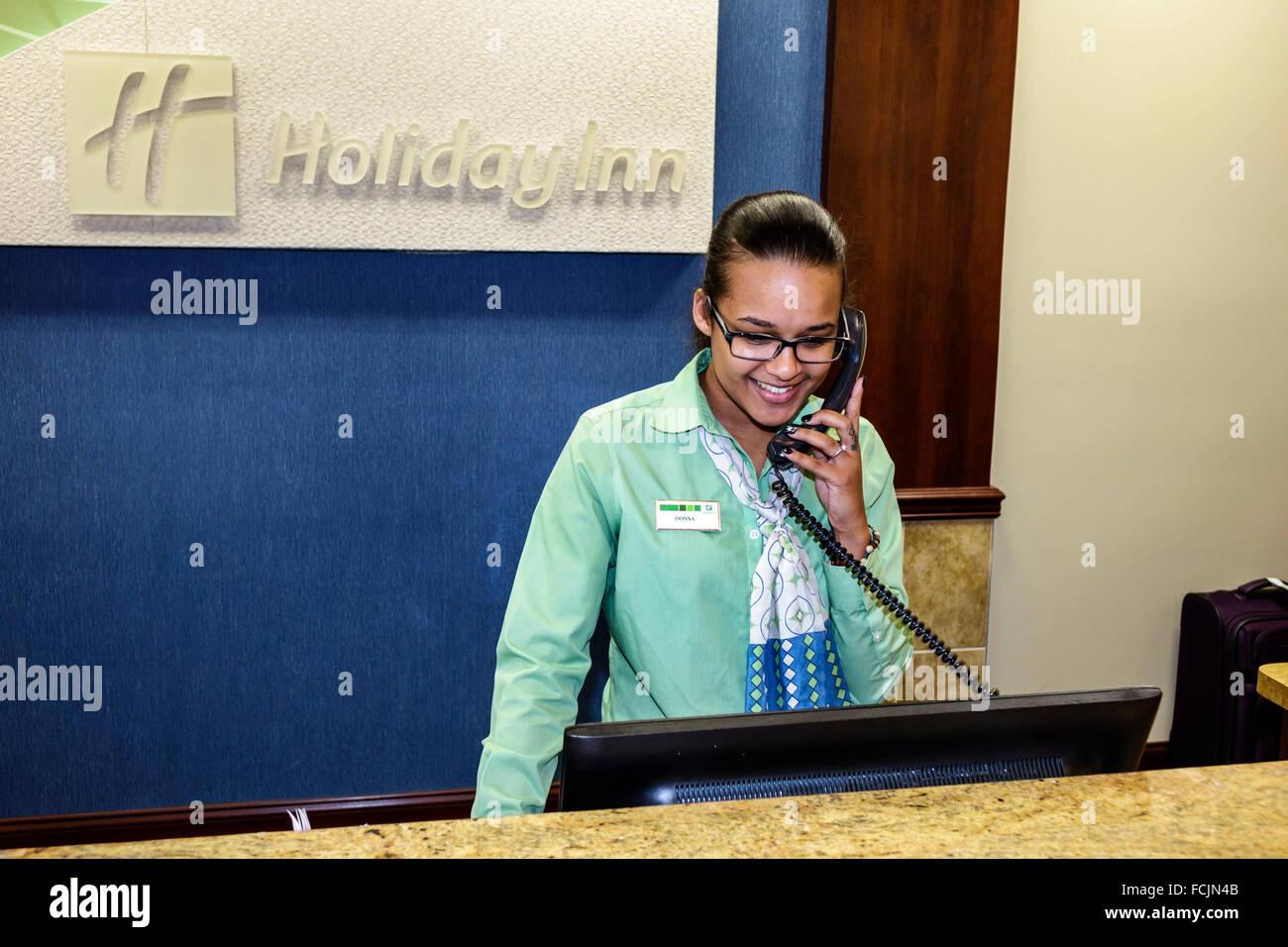 Orlando Kissimmee Orlando Florida Holiday Inn hotel inside lobby front desk Black woman employee telephone phone - Stock Image
