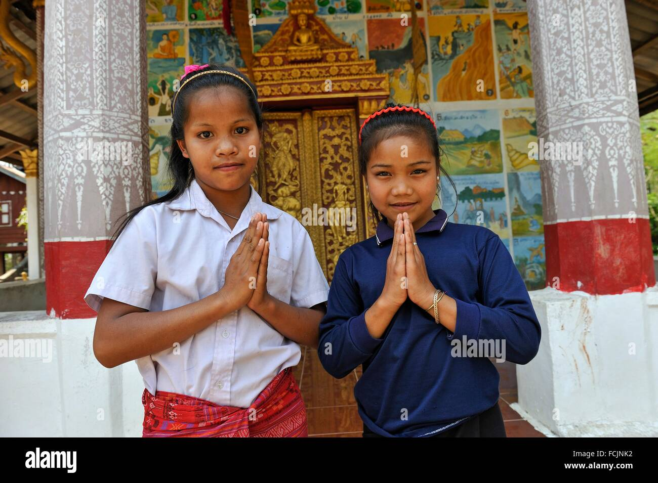 two little girls beside the temple of Ban Baw, a traditional Lao Loum village between Luang Prabang and Pakbeng, - Stock Image