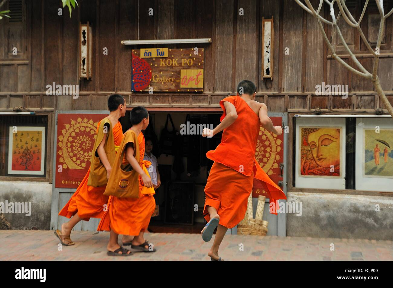 novice monks beside the Kok Po Art Gallery, Luang Prabang, Laos, Southeast Asia. - Stock Image