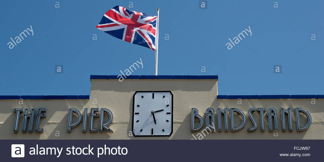 Union Jack flying above The Pier Bandstand Building on the Esplanade, Weymouth, Dorset, England - Stock Image