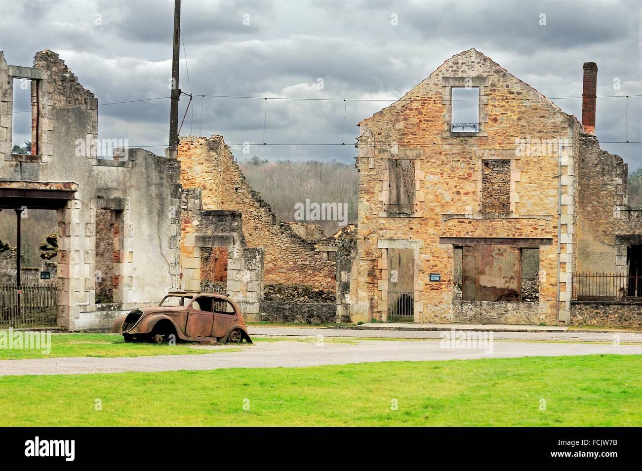 building ruins and remains of Peugeot 202 car, Oradour-sur-Glane, Haute-Vienne Department, Limousin, France. - Stock Image