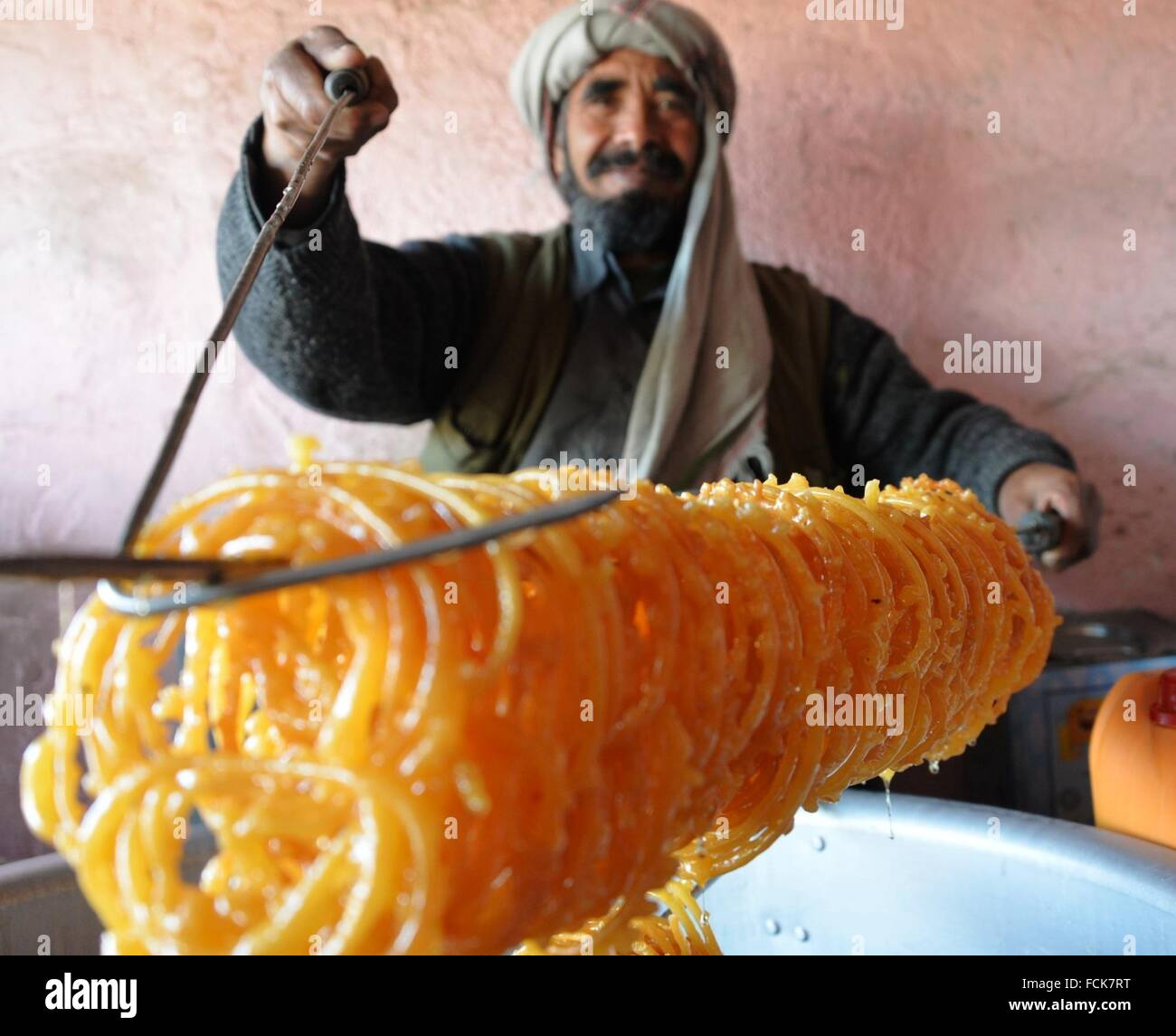 Ghazni, Afghanistan. 23rd Jan, 2016. An Afghan man presents traditional  sweets called Jalebi at a traditional
