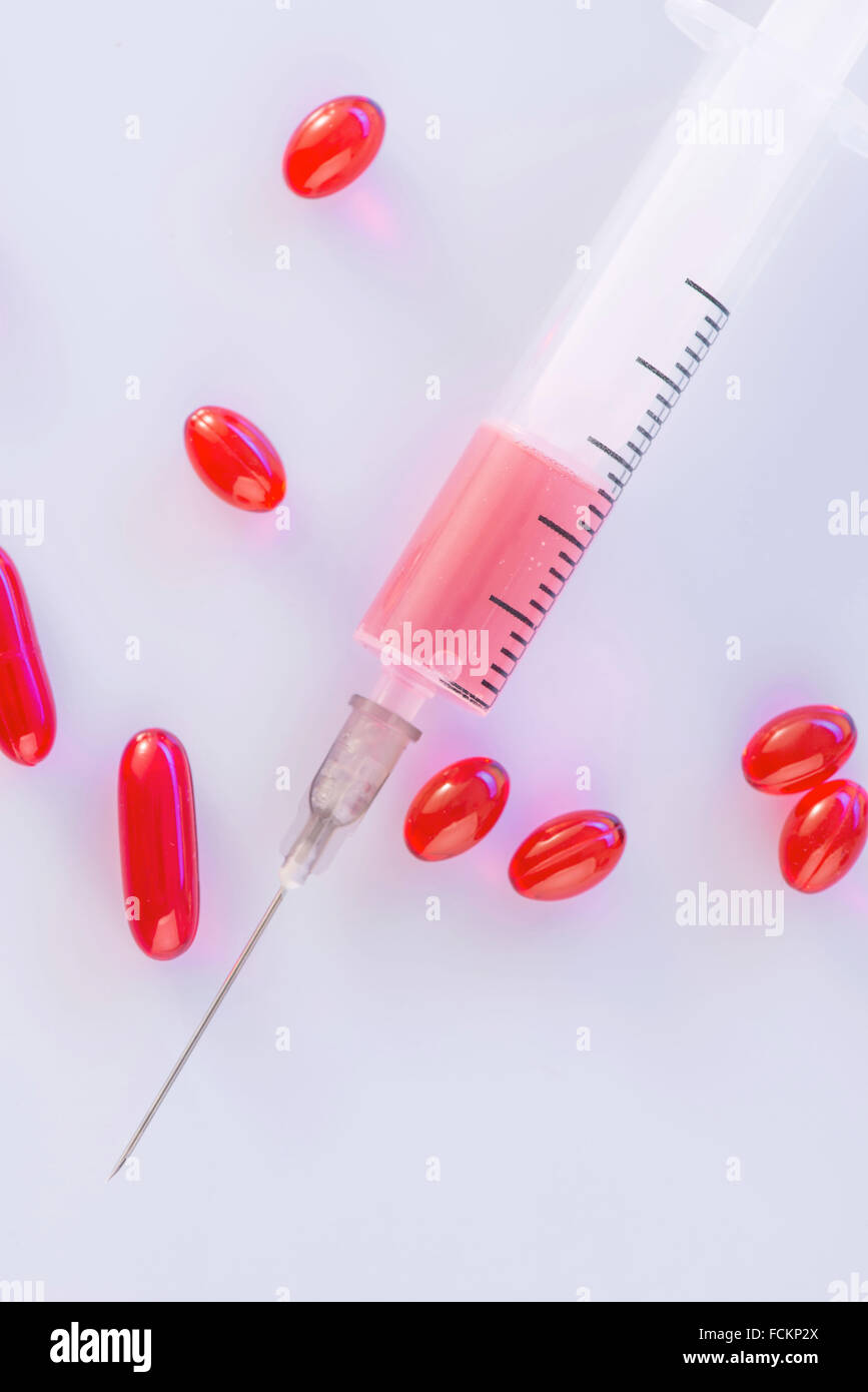 Red pills and syringe on the surface. - Stock Image