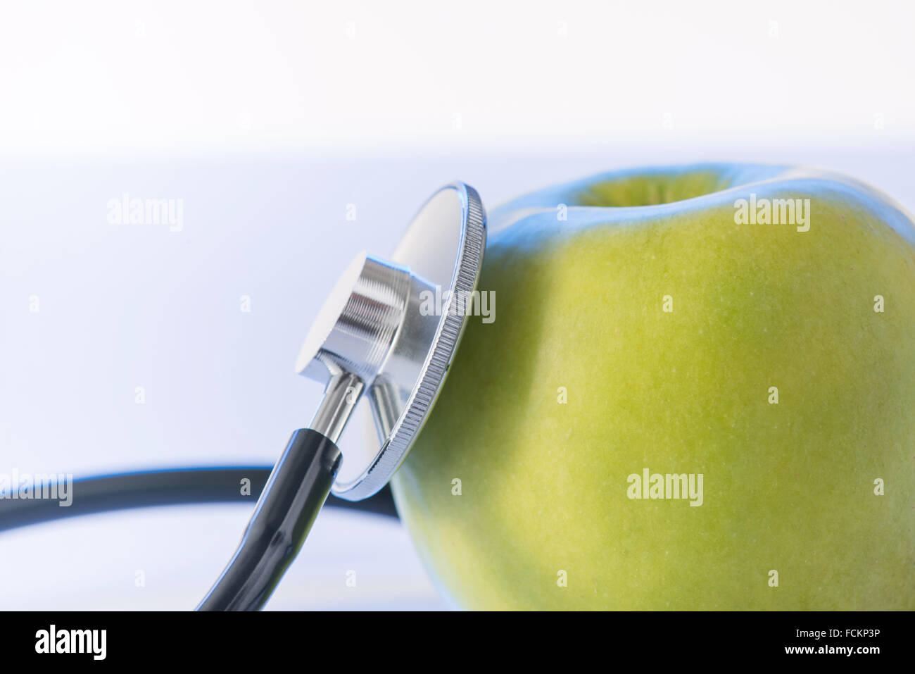 Green apple and stethoscope. - Stock Image