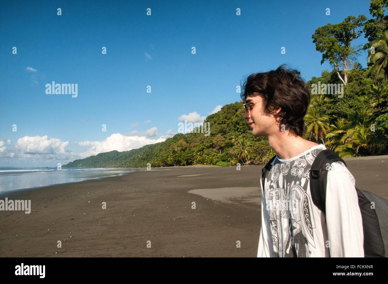 young male European traveller on empty beach, wild coast of the Pacific Ocean, Corcovado National Park, Costa Rica,. - Stock Image