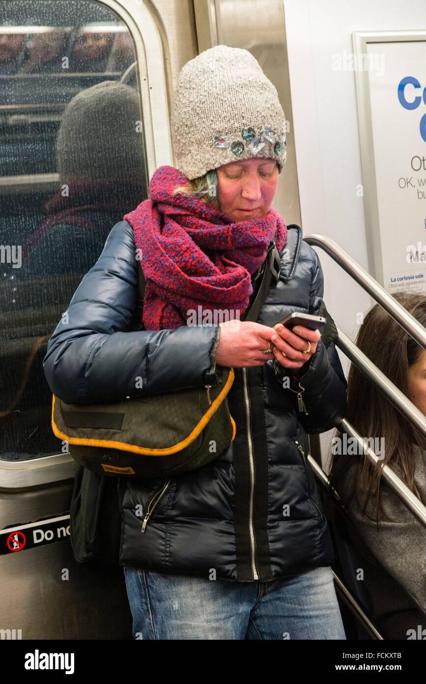 Subway, New York, USA. Warmly dresses caucasian girl using her smartphone, while commuting by subway through Manhattan. - Stock Image