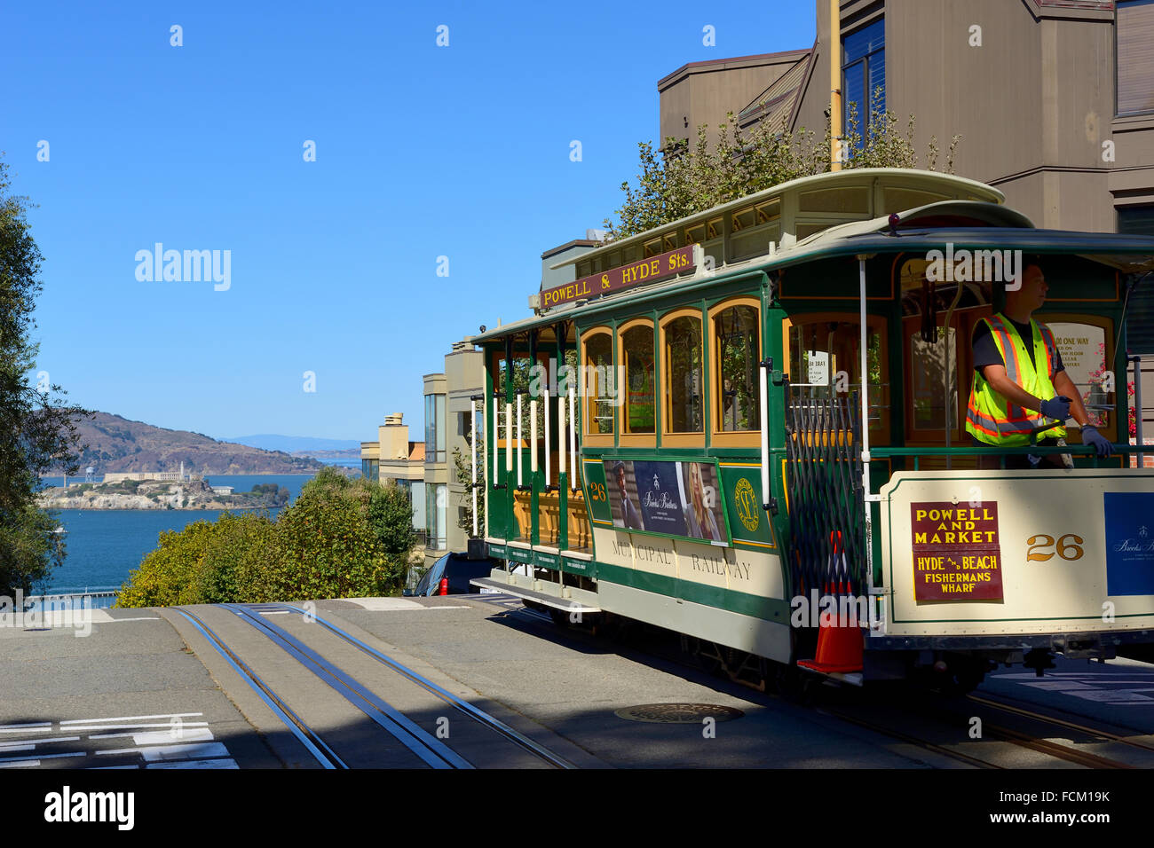 Cable car on Hyde Street at junction with Lombard Street, with distant view of Alcatraz Island, San Francisco, California, - Stock Image