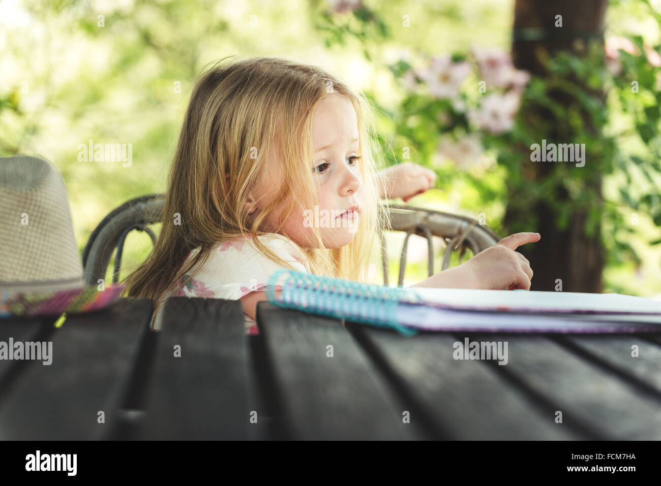 Beautiful blond girl in the garden at sunny summer day - Stock Image