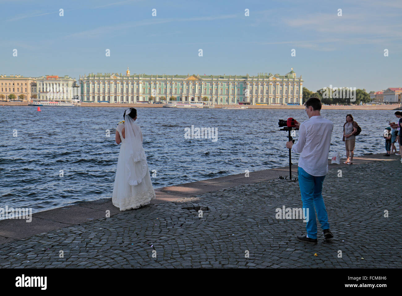 A bride being photographed on the banks of the Neva River, opposite the Winter Palace in Saint Petersburg, Russia. - Stock Image