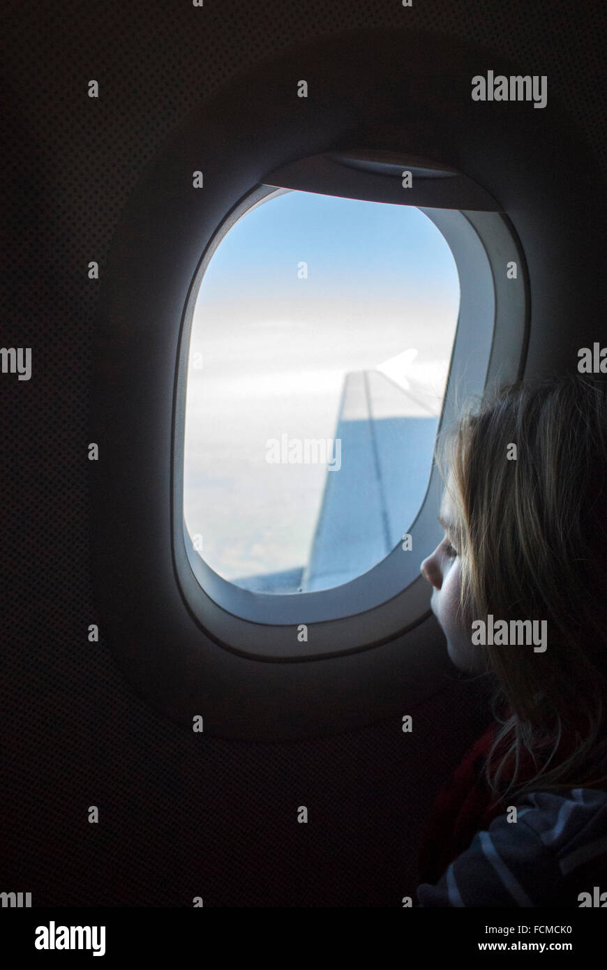 Young girl looking out of airplane window while plane is flying. - Stock Image