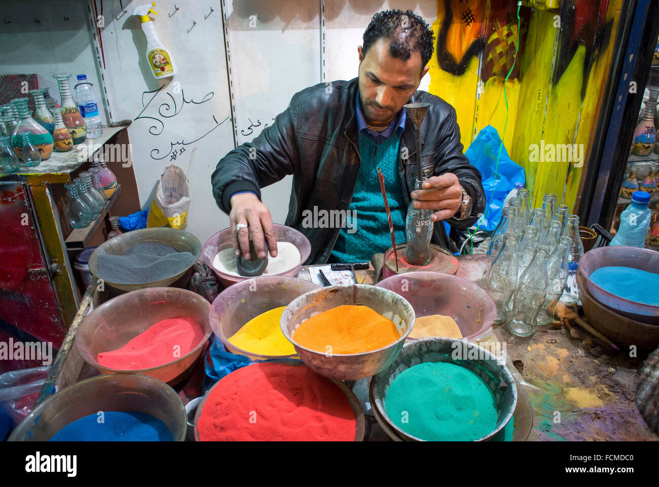 A street sand artist in the Downtown area of Amman fills bottles with sand as gifts in Amman, Jordan. - Stock Image
