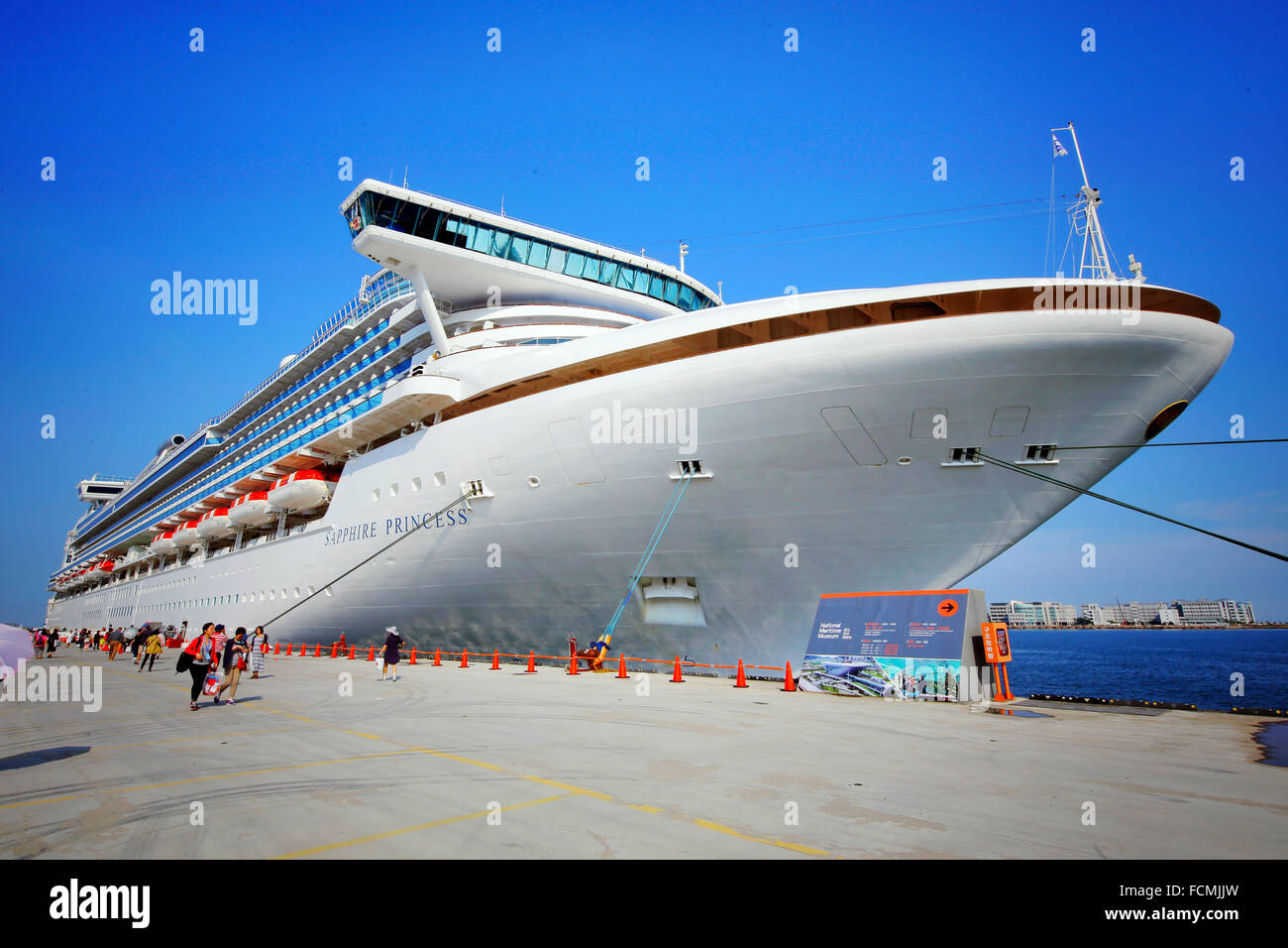 Cruise ship moored at dock against blue sky - Stock Image