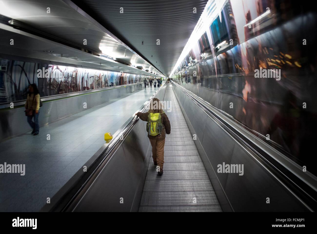 Young girl using the walkway between terminals at Frankfurt Airport, Germany. - Stock Image
