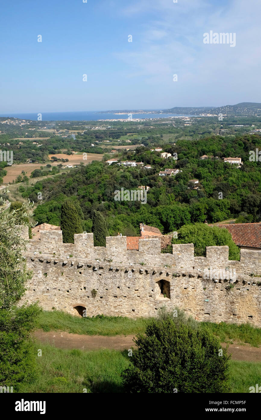 Grimaud, South of France, showing part of the castle wall and view towards the Cote d'Azur. - Stock Image