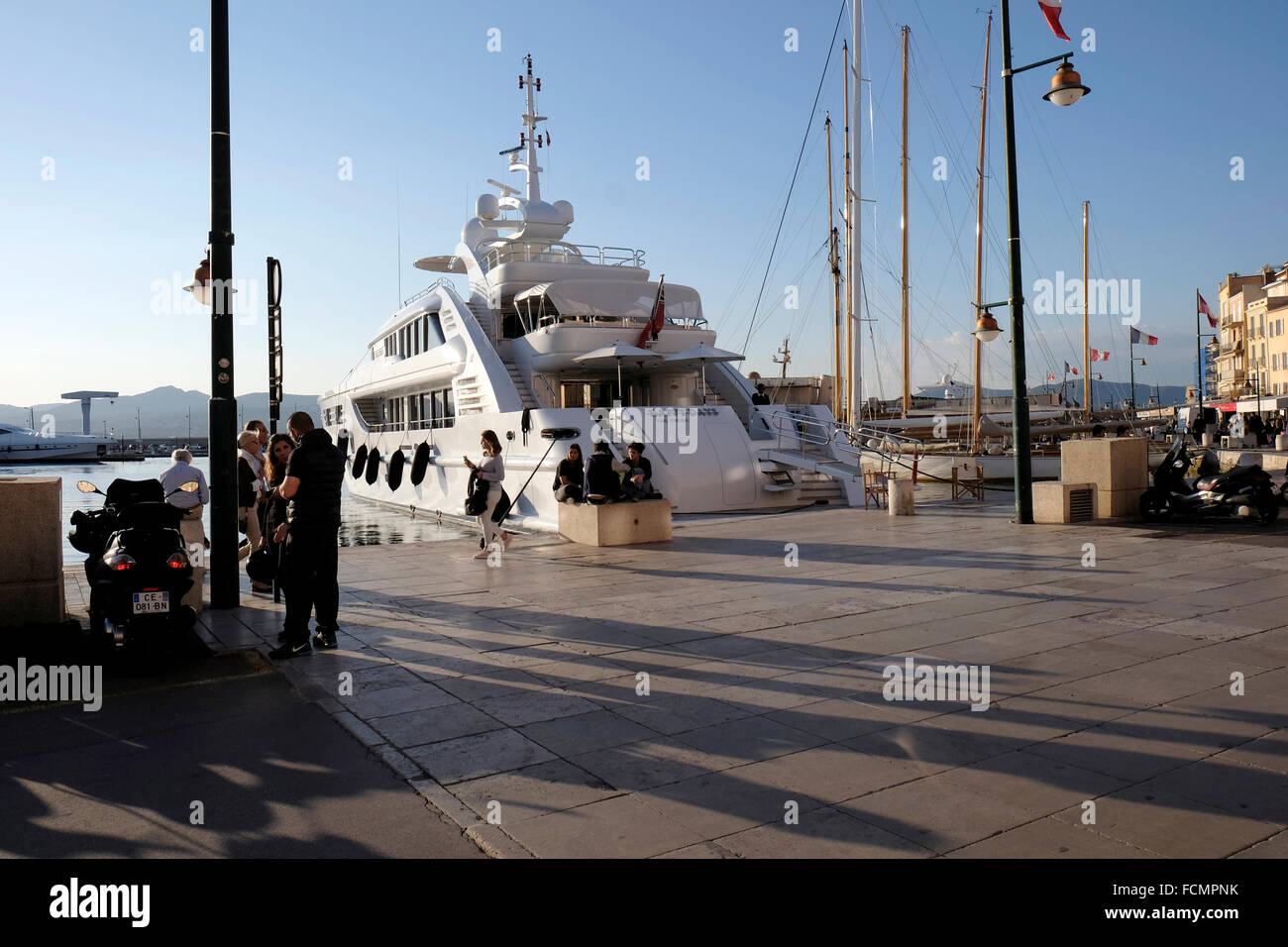 Luxury yacht moored in the harbour at St Tropez with young people sitting and passers by.  Evening shot. - Stock Image