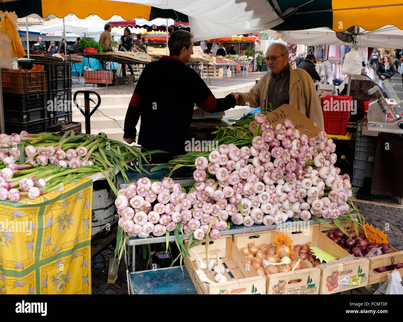 Stall-holder shaking hands with acquaintance at a garlic stall in the market at Fréjus, South of France. - Stock Image