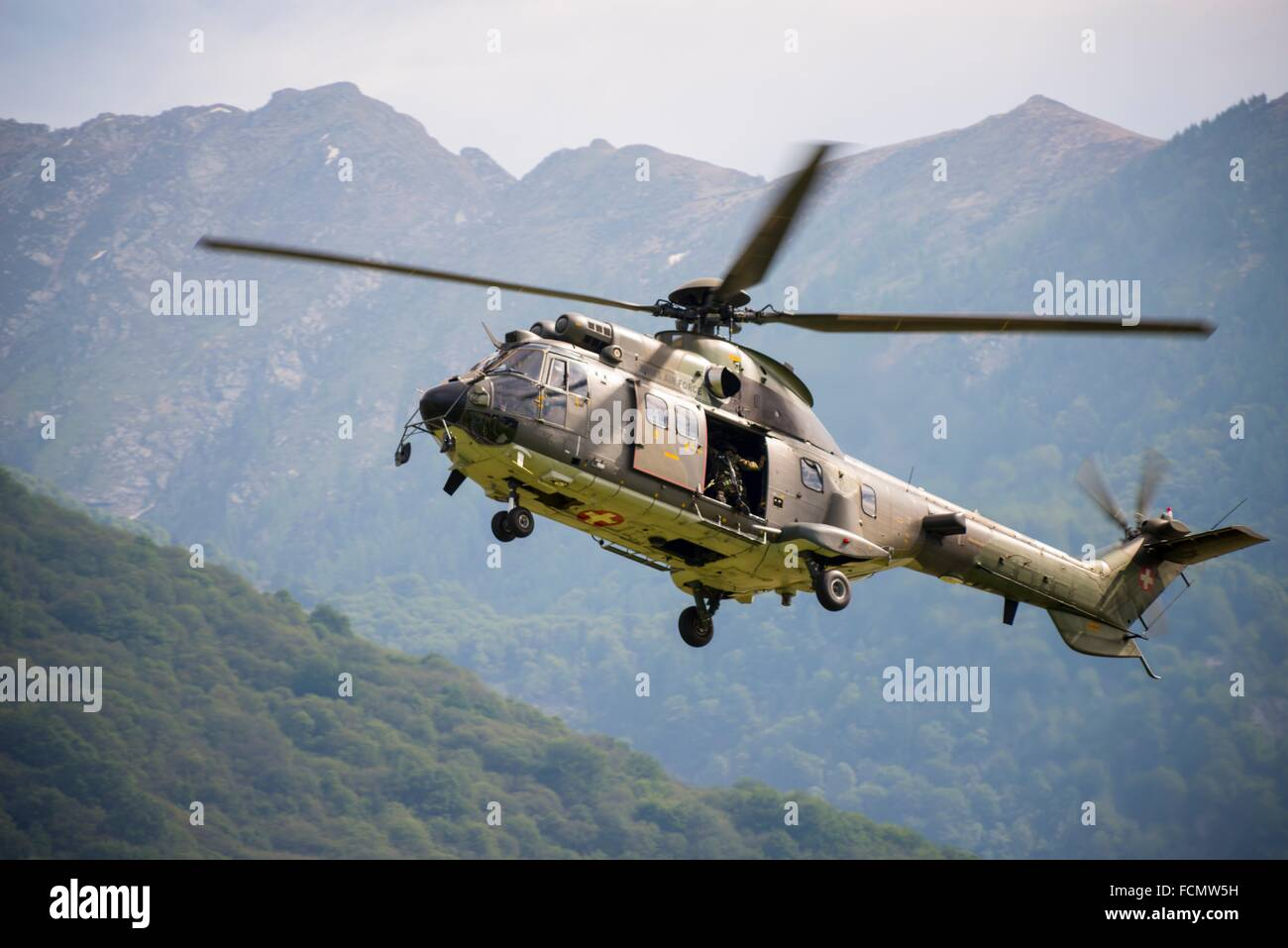 Military Helicopter flying and Swiss Alps in Ticino, Switzerland. - Stock Image