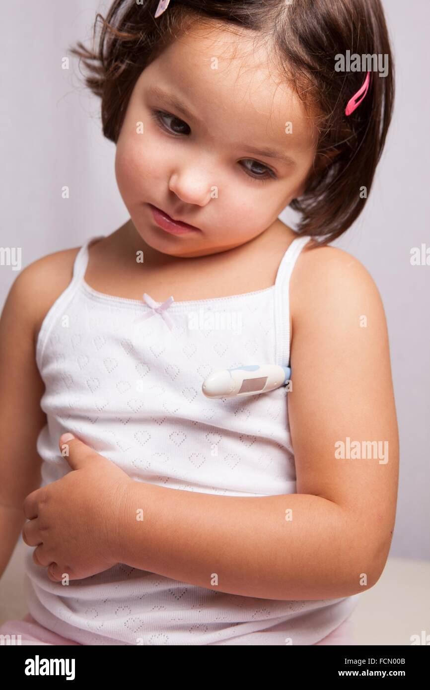 Unwell little girl with electronic thermometer. Isolated over white background. - Stock Image