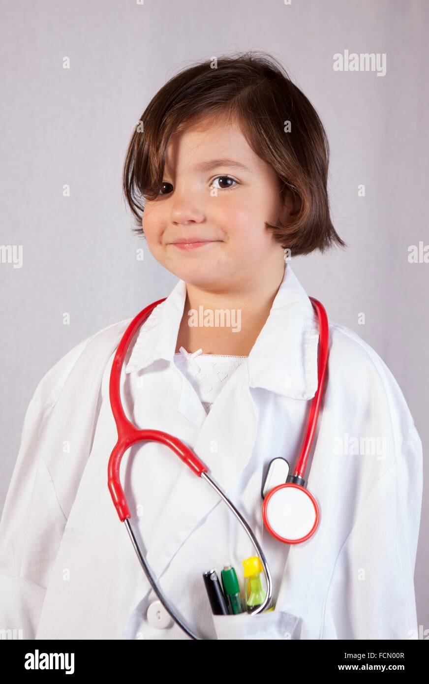 Little girl dressed with a white lab coat and stethoscope. Isolated over white background. - Stock Image