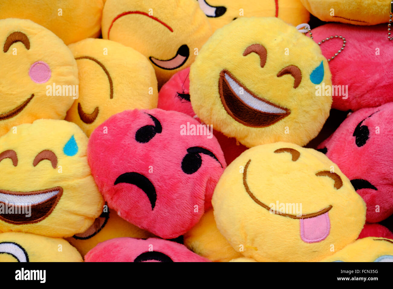 Angry face in a crowd of happy faces - Stock Image