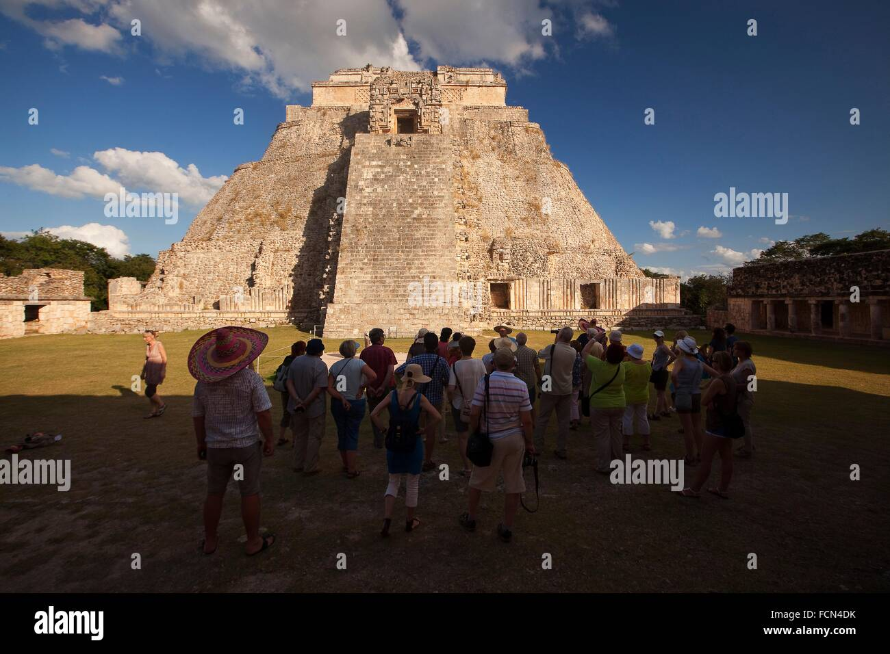 Tourists walking around the Pyramid of the Magician, Maya archeological site Uxmal, Yucatan, Mexico, Central America. - Stock Image