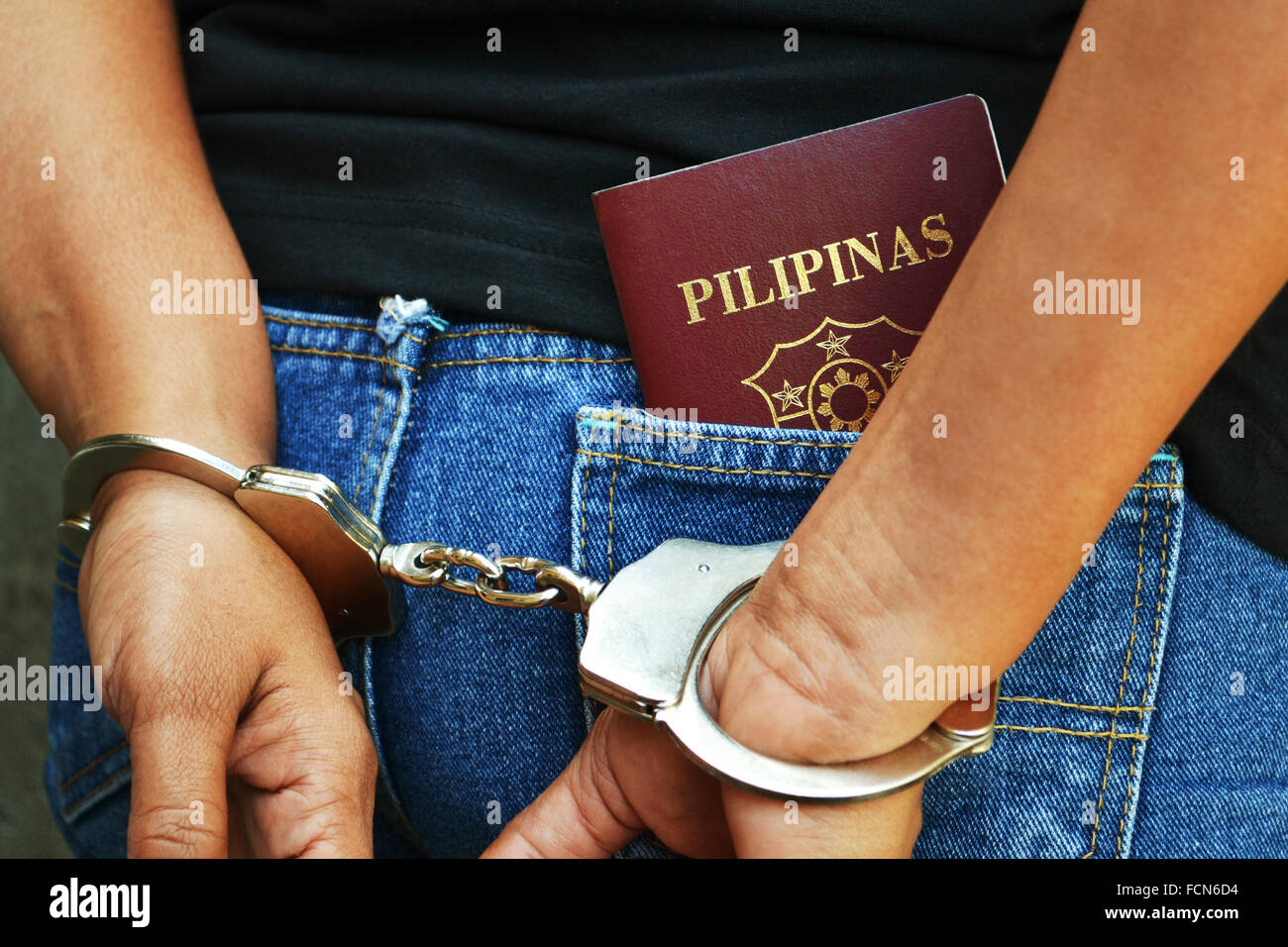 Arrested Filipino citizen with handcuffs and Filipino passport in the rear pocket - Stock Image