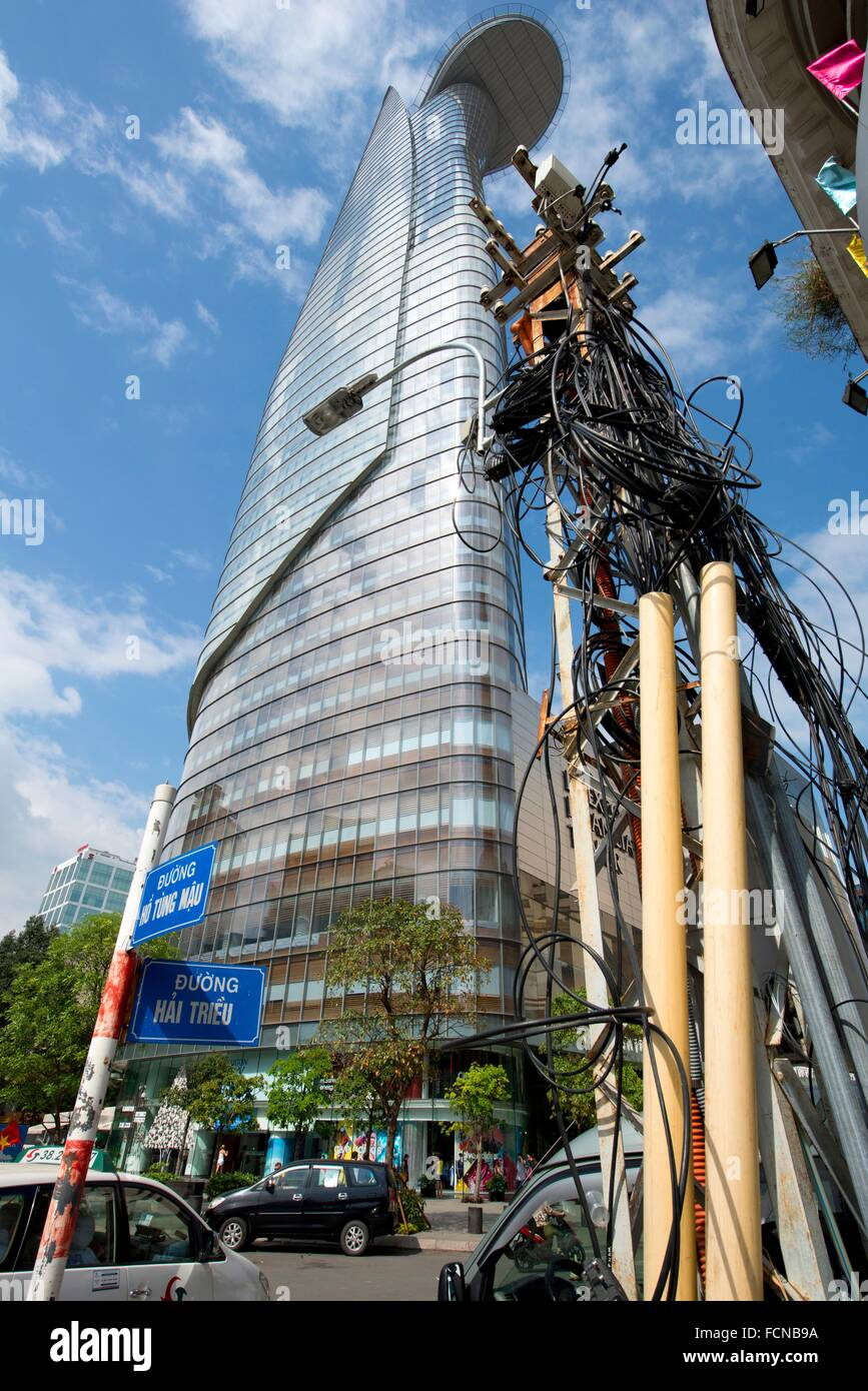 Tangle of electrical cables on pole by Bitexco Financial Tower, Ho Chi Minh City (HCMC), Vietnam. - Stock Image