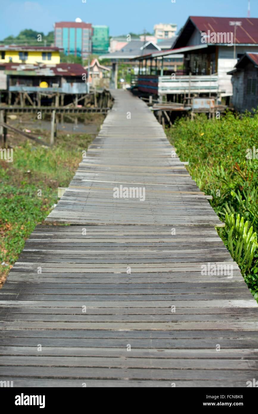 Wooden walkway bridge to village with city in background, Bandar Seri Begawan, Brunei. - Stock Image