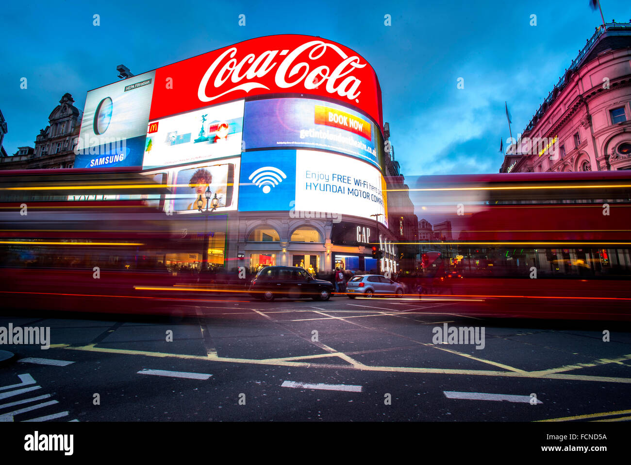 Buses and Taxis whizz past The world famous Advertising boards in Piccadilly Circus in London. - Stock Image