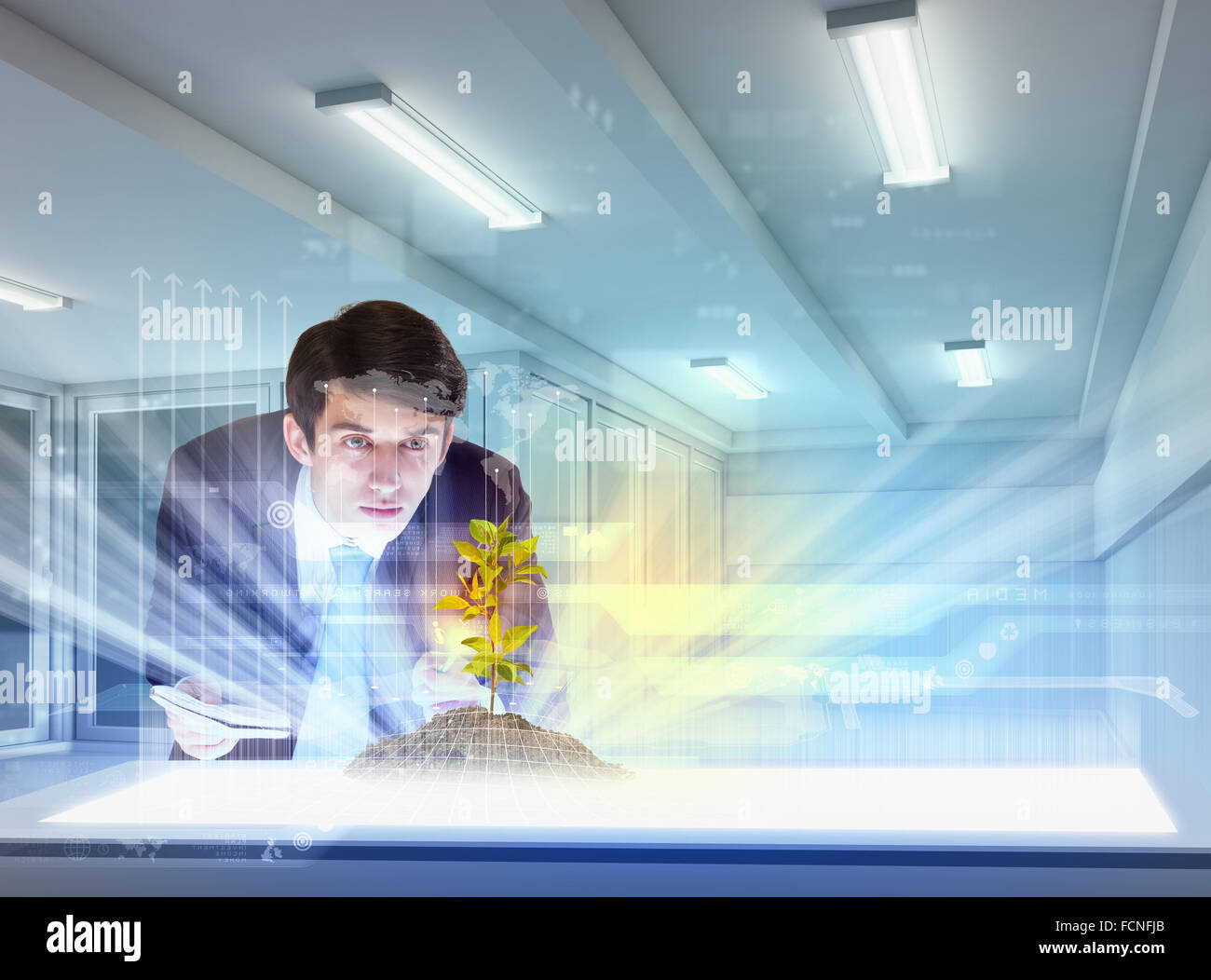 young businessman looking at high-tech image of sprig - Stock Image