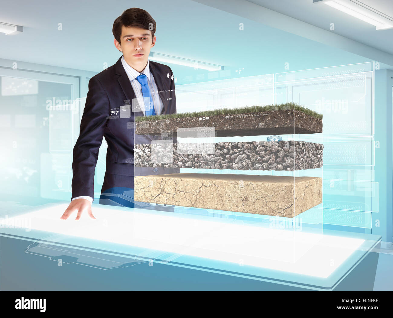 Image of young businessman looking at high-tech picture of topsoil - Stock Image