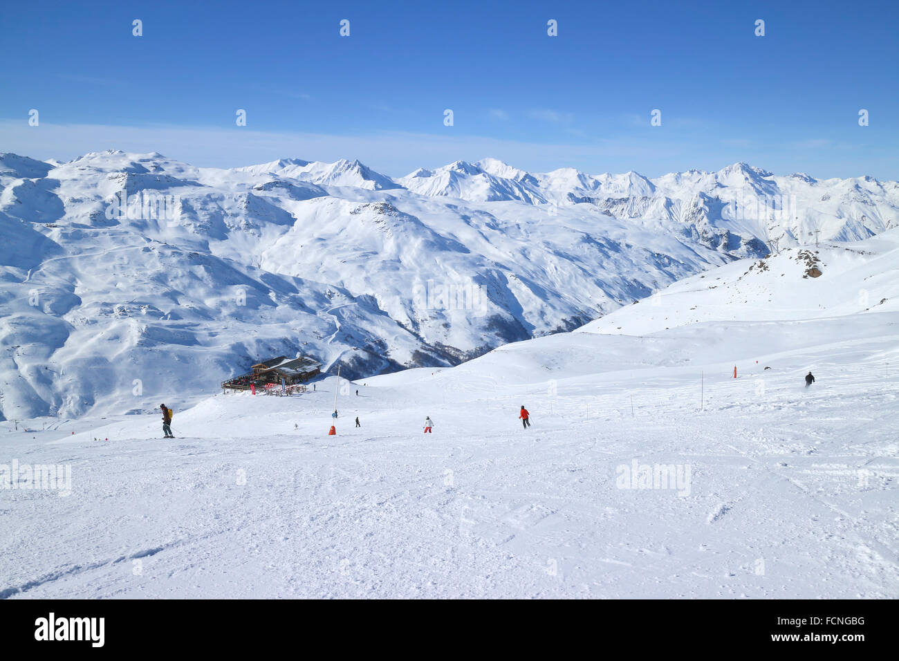 Skiers on ski slopes in high Alps resort of Three Valleys France, apres ski chalet, with snowy mountain peaks against Stock Photo