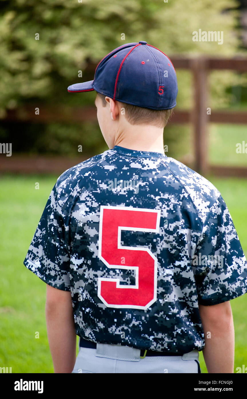 Close up of a baseball player outside from behind in a camo jersey looking sideways - Stock Image