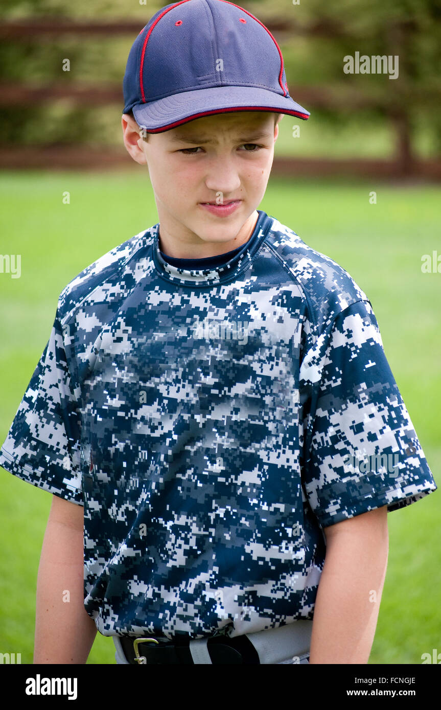Young baseball boy outside with camo uniform looking away from camera - Stock Image