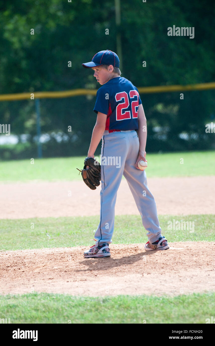 Youth baseball boy pitching on the mound during a game - Stock Image