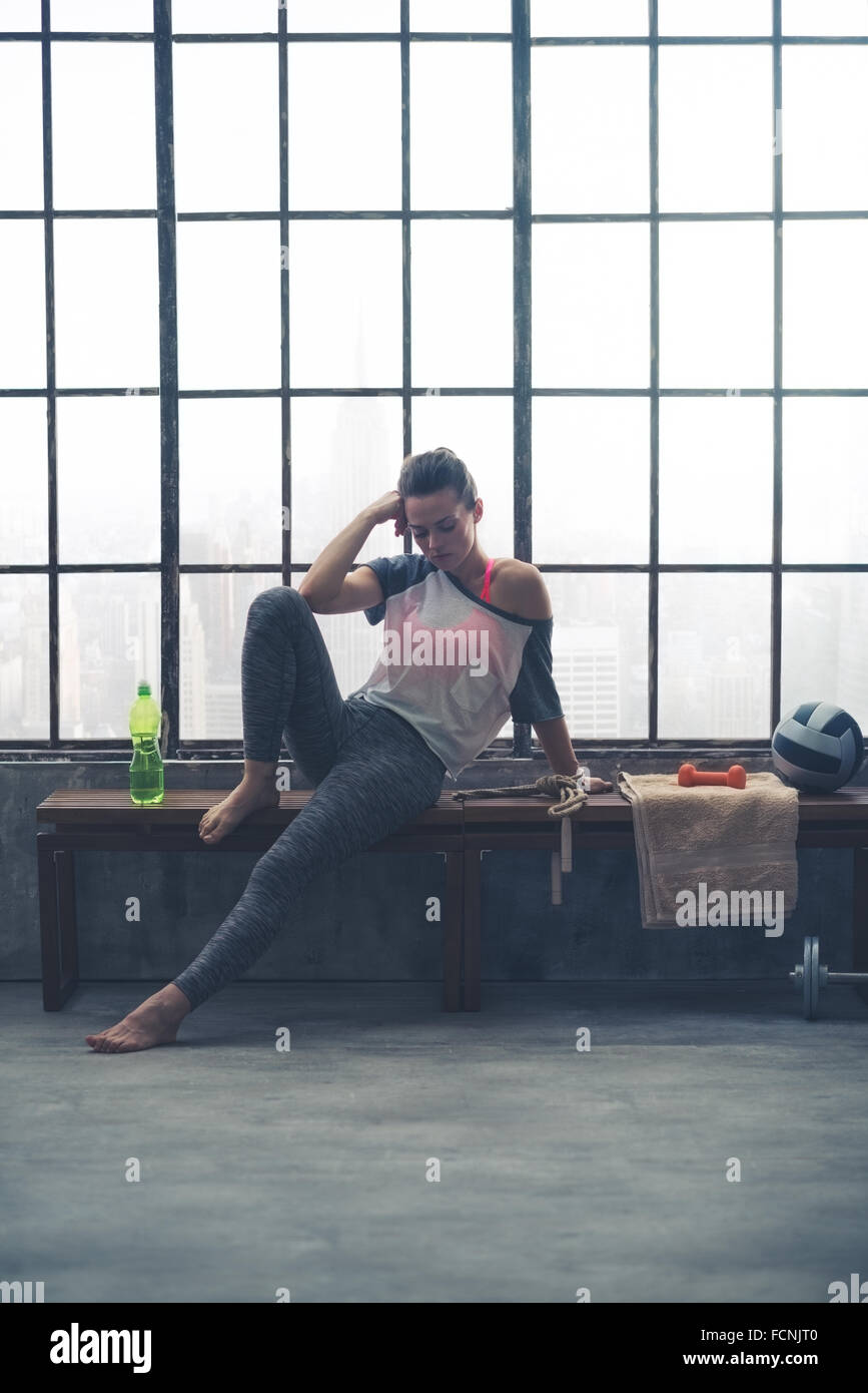 A fit, healthy woman in workout gear is sitting on a bench, resting one elbow on her bent knee, and her head on - Stock Image