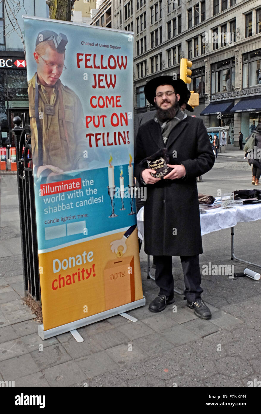 A religious Jewish man encourages other Jews to wear phylacteries - tefillin - in UNion Square Park in New York - Stock Image