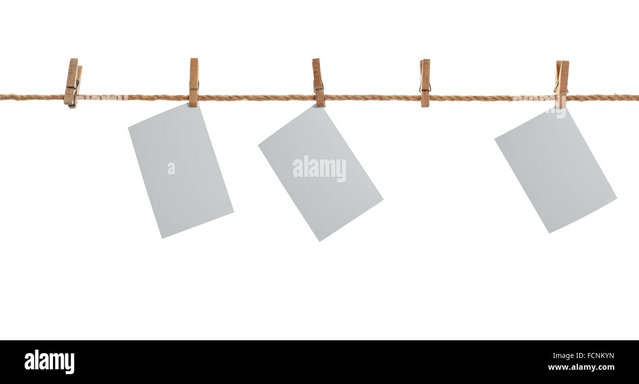 grey photo paper. Hanging on a clothesline with clothespins. On  white background - Stock Image