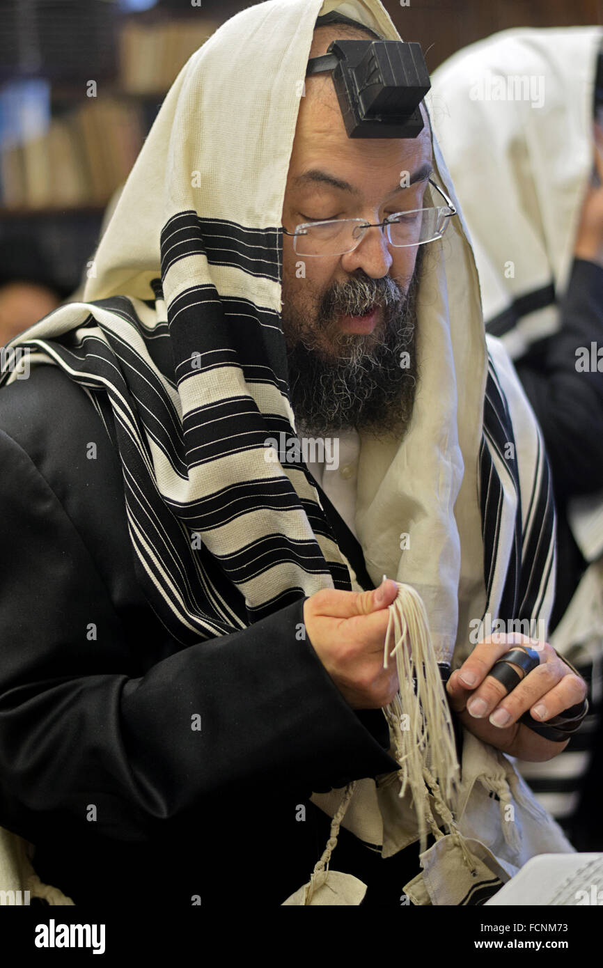 A religious Jewish man lead a small congregation in morning prayers in Crown Heights, Brooklyn, New York - Stock Image