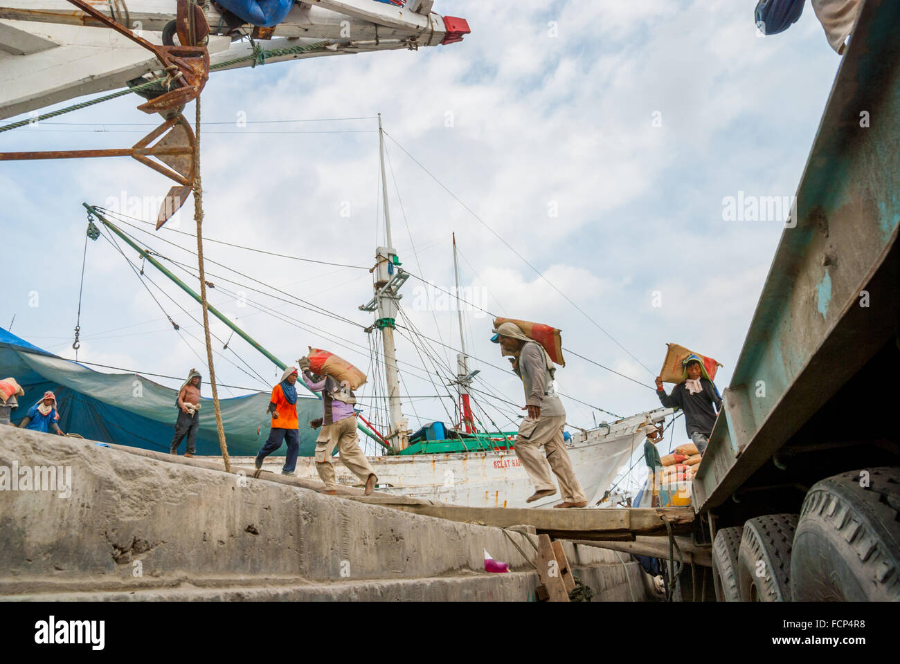 Workers loading cements onto wooden ship at Sunda Kelapa traditional harbour. Jakarta, Indonesia. - Stock Image