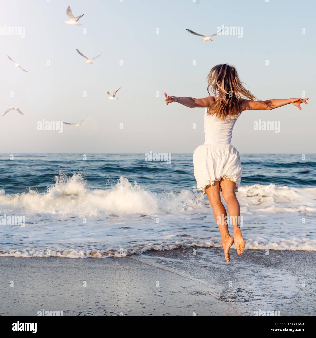 Beautiful girl  jumping on sea - Stock Image
