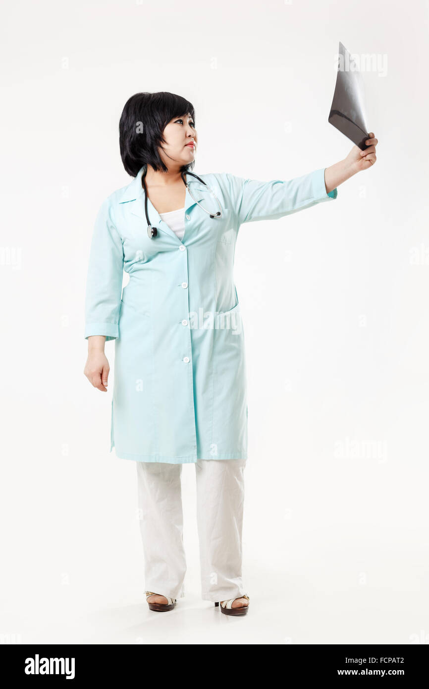Curvy woman doctor standing considers the results of radiology department, x-ray skull picture outstretched arm, - Stock Image