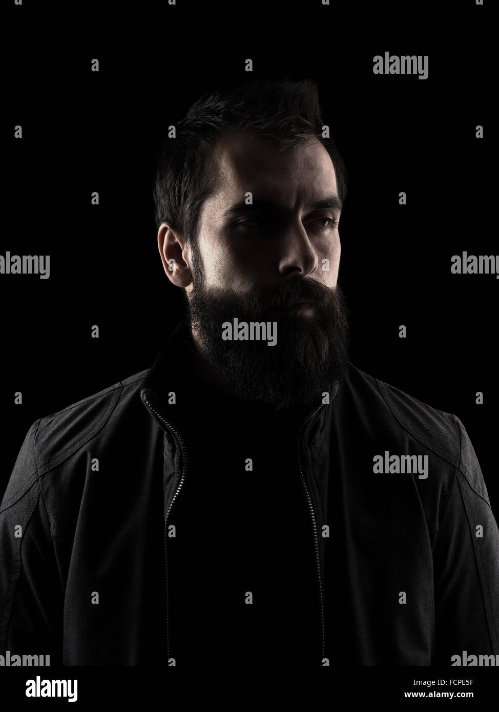 Desaturated serious bearded hipster looking away. High contrast low key dark shadow portrait isolated over black - Stock Image