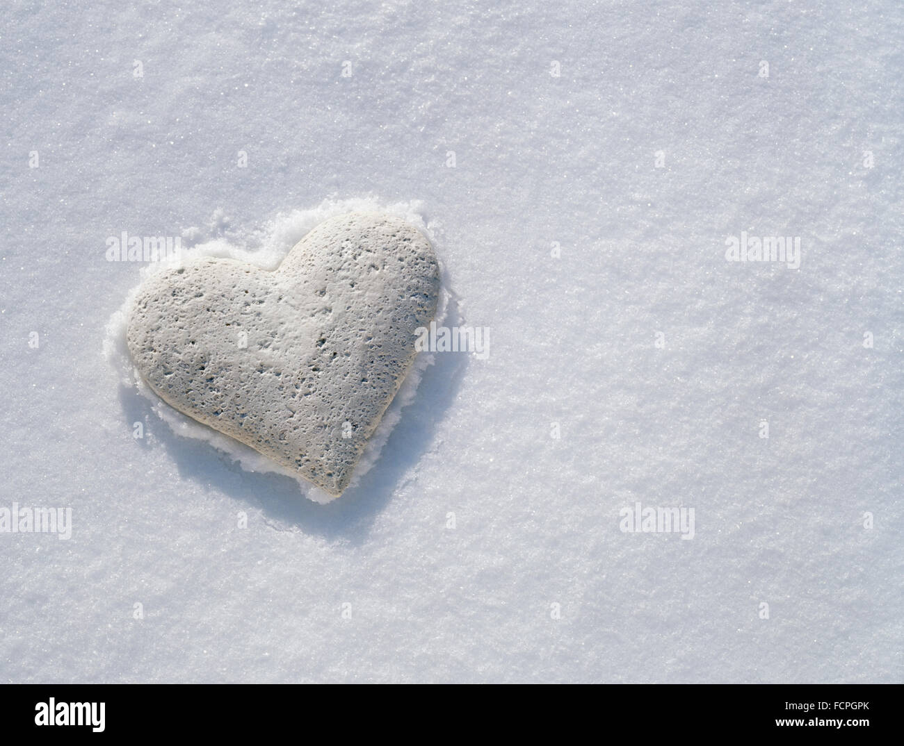 White stone heart resting on frozen crust of pristine snow. - Stock Image