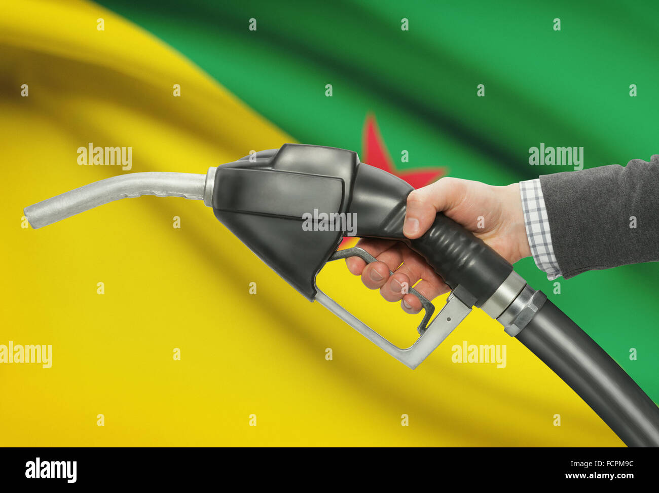 Fuel hand in nozzle flag on French Guiana pump with background qUzMSVp