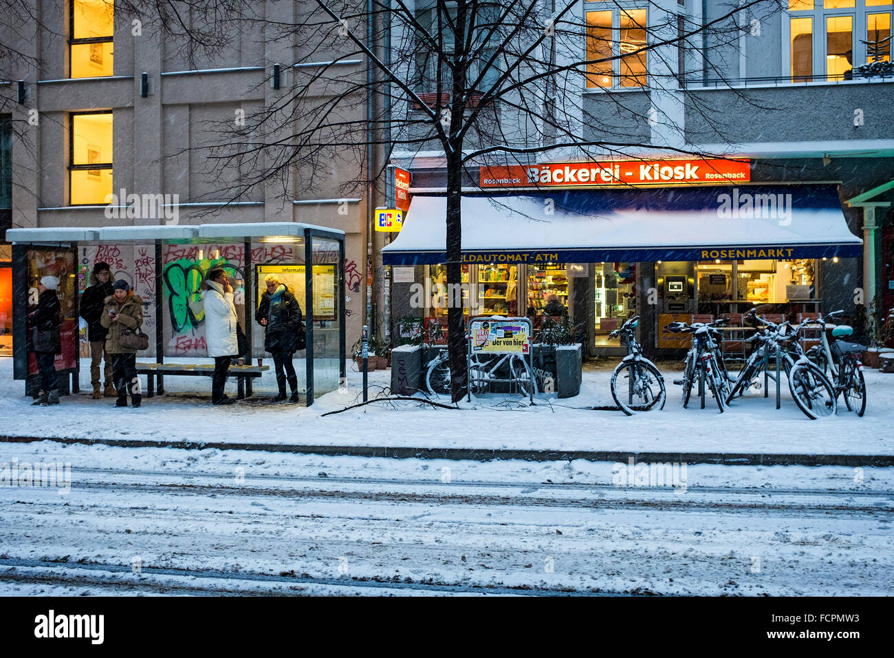 Berlin City Street, Cafe bakery and people sheltering at tram stop shelter during heavy snow fall in Winter - Stock Image