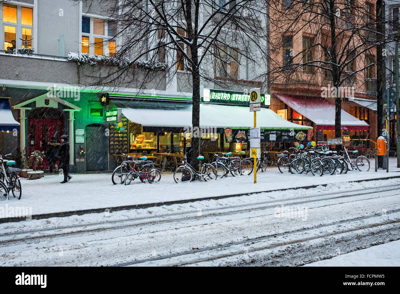 Berlin City Street, Cafe Bistro and tram stop after heavy snow fall in Winter - Stock Image