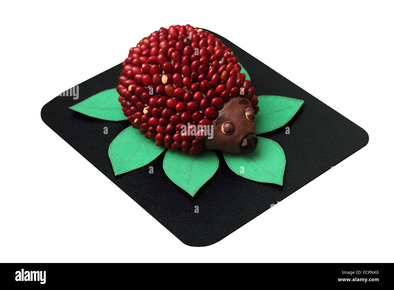 Toy hedgehog made from plasticine and beans isolated on white - Stock Image